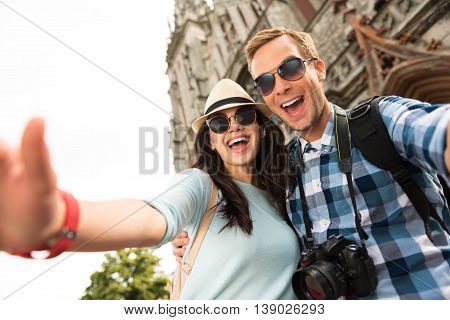 Express yourself. Positive overjoyed tourists smiling and having a walk while traveling together