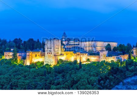 Night panorama with Alhambra Palace illuminated at night in Granada, Andalusia - Spain