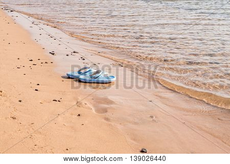 Beach shoes on a sandy beach in front of the sea