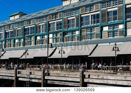 Finger wharf restaurant in Woolloomooloo bay with unrecognisable people in the distance. Sydney Australia