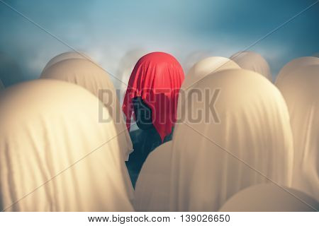 Uniqueness and leadership concept with abstract human head under red piece of cloth on blurry background. 3D Rendering