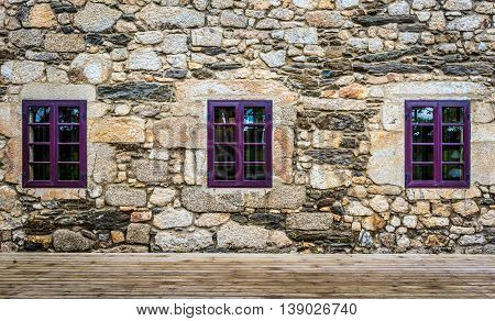 Purple Window On Medieval Castle Made Of Stone And Rocks.