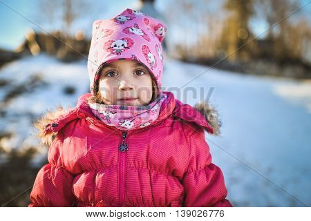 Little girl in winter clothes standing in mountain ski resort. A child with cap scarf and winter jacket is looking at the camera outside in snowy nature.