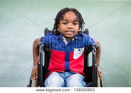 Portrait of handicapped boy against board in classroom