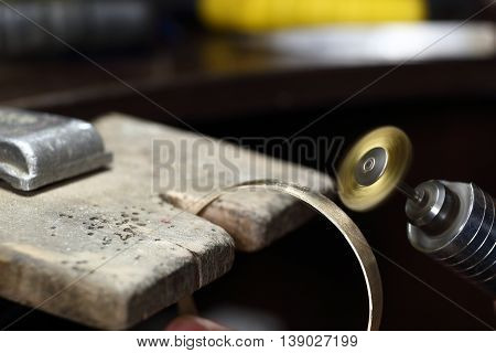 Jeweller working with bracelet. Jewelry workplace, workshop, manufacturing.