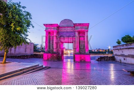Panoramic view over the Roman gate of the bridge illuminated at night in Cordoba - Andalusia Spain
