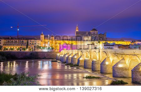 Panoramic view over the Roman bridge illuminated at night in Cordoba - Andalusia, Spain