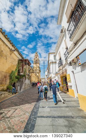 Cordoba, Spain - May 20, 2016: Traditional architecture of cordoba and tourists walking on the street, in a day time