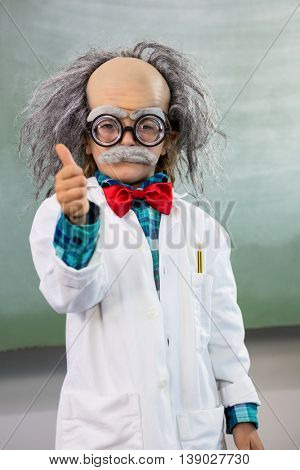 Boy dressed as scientist gesturing thumbs up sign in classroom