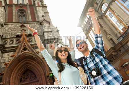 Playful mood. Positive content smiling tourists holding hands up and expressing joy while having a walk