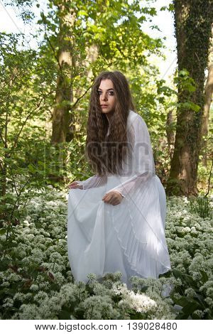 Beautiful woman wearing a long white dress tip toeing through the flowers in a forest