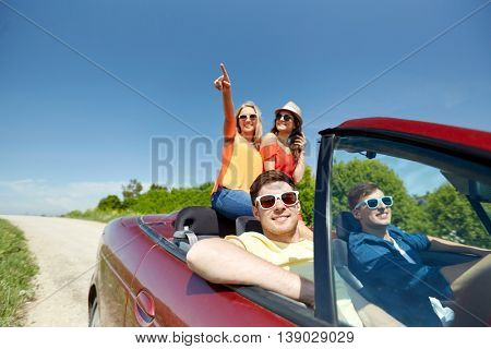 leisure, road trip, travel and people concept - happy friends driving in cabriolet car along country road and pointing finger to something