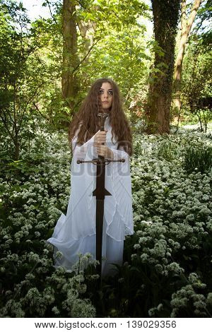 Beautiful woman wearing a long white dress holding a medieval sword in a forest of white flowers