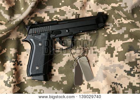 Gun and army token on khaki background