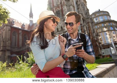 Glad to be together. Joyful delighted couple smiling and bonding to each other while resting in the city