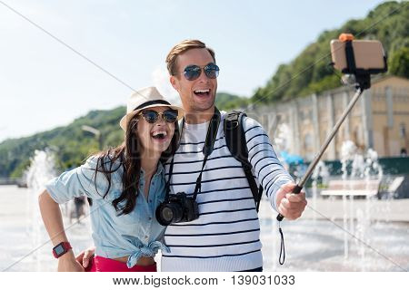 On the edge of joy. Positive smiling overjoyed couple smiling and making selfies near fountain while feeling glad