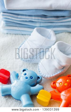 babyhood, childhood, toys, clothing and object concept - close up of baby rattle with bootees and clothes for newborn boy on towel