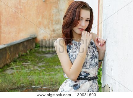 portrait of a pensive girl on a background of old wall