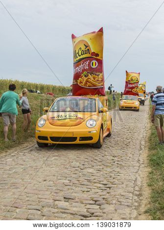 Quievy, France - July 07 2015: Mc Cain Caravan during the passing of the Publicity Caravan on a cobblestone road in the stage 4 of Le Tour de France on July 7 2015 in Quievy France. Mc Cain is a market leader in frozen products made from potatoes.