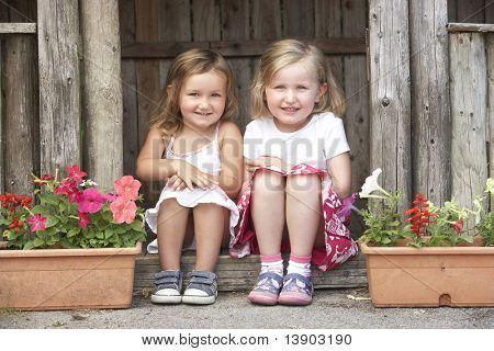 Two Young Girls Playing in Wooden House