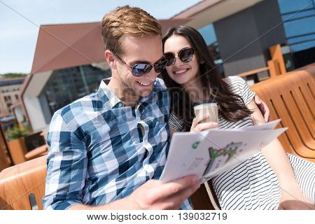 Happy together. Pleasant cheerful smiling couple sitting on the bench and using city map while drinking coffee