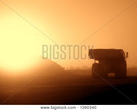 Truck on a Dusty Construction Site at Sunset