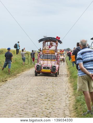 Quievy, France - July 07 2015: Cochonou Caravan during the passing of the Publicity Caravan on a cobblestone road in the stage 4 of Le Tour de France on July 7 2015 in Quievy France. Cochonou is an important French brand of short dry sausages.