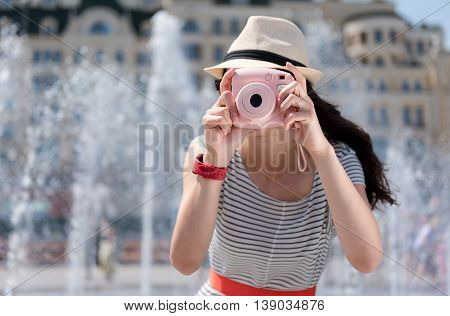 Just smile. Pleasant woman holding camera and making photos while standing near fountain