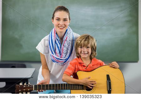 Portrait of young teacher assisting boy to play guitar in classroom
