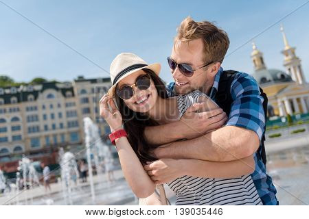 Love you so much. Pleasant happy delighted couple smiling and embracing while standing near fountain