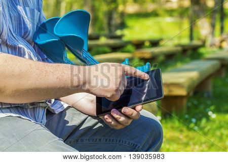 Disabled man with tablet PC and crutches on the bench
