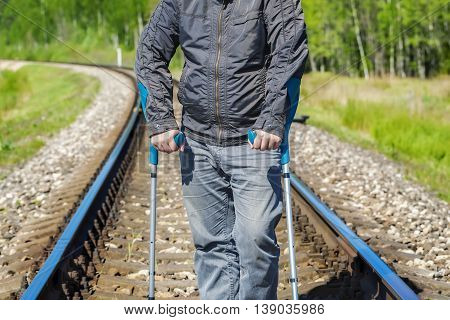 Disabled man with crutches on the railway .