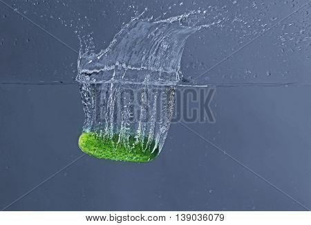 Fresh cucumber falling in water on dark background