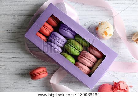 Different colorful macaroons in gift box on wooden background