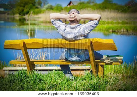 Man with tablet PC and books relaxing on bench near river