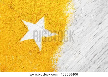 Turmeric powder with star silhouette on light wooden background