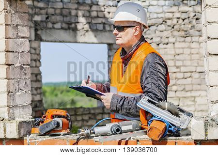 Construction worker writing near tools in unfinished building