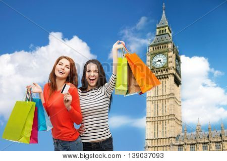 shopping, sale, tourism and people concept - two smiling teenage girls with shopping bags and credit card over big ben clock tower background