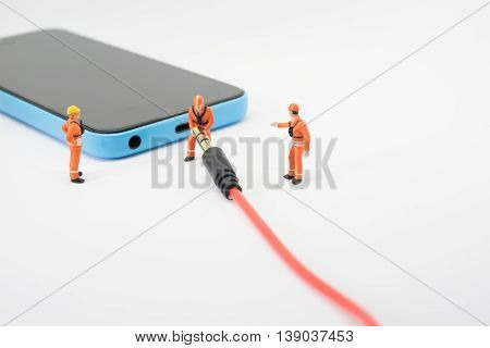 Worker With Mobile Phone Or Smartphone To Removed Audio Cord.