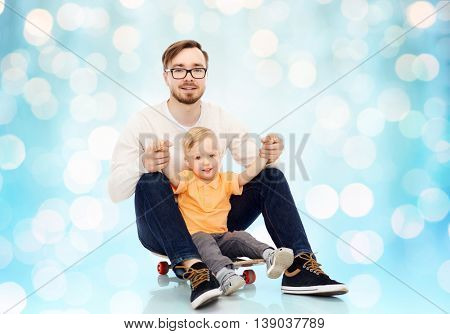 family, childhood, fatherhood, leisure and people concept - happy father and and little son on skateboard over blue holidays lights background