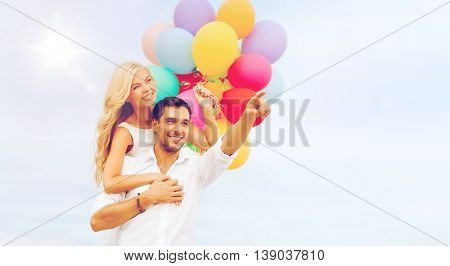 summer holidays, celebration and dating concept - couple with colorful balloons at sea side