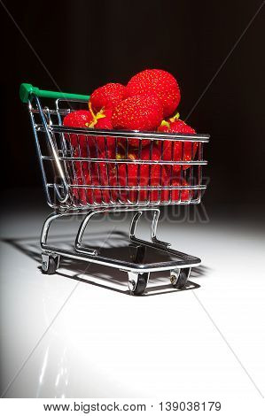 ripe red strawberries in supermarket trolley on black and white background