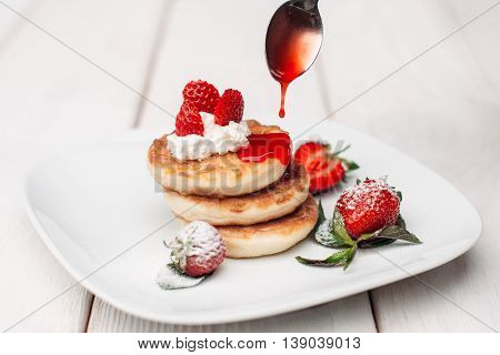 Pancake dessert pouring with strawberry topping. Appetizing meal with flapjacks pile, cream and fresh berries. Sweet food decor at restaurant