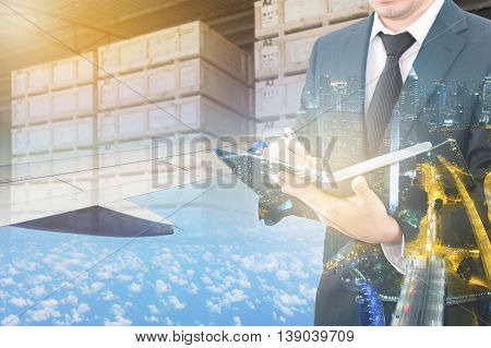Double Exposure Of Businessman Writing Notebook And Business Center City With Blurred Cargo In Woode