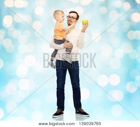 family, childhood, fatherhood, healthy eating and people concept - happy father and and little son with green apple over blue holidays lights background