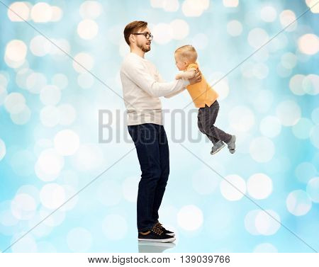 family, childhood, fatherhood, leisure and people concept - happy father and little son playing and having fun over blue holidays lights background