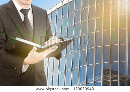 Businessman checking report with business tower background and green graph up business concept