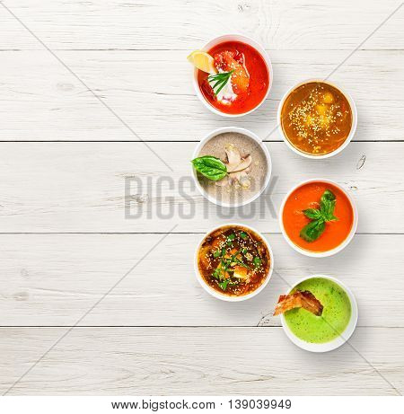 Variety of restaurant hot dishes, healthy food. Japanese miso, asian fish soup, russian borscht, english pea soup with bacon, mushroom soup, spanish gazpacho at white wood, top view with copy space