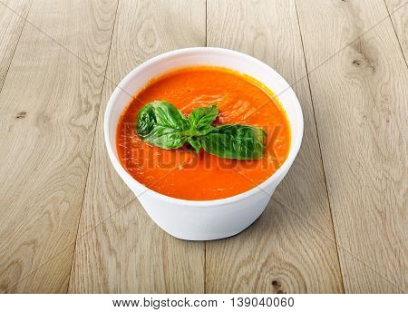 Spanish cuisine hot food delivery - tomato diet cream soup gazpacho at wood background in white plastic plate