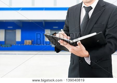 Professional Businessman Booking With Blurred Distribution Warehouse Background, Industrial Business